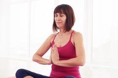 Donna pacifica che medita mentre sedendosi sulla stuoia nella palestra fotografia stock libera da diritti