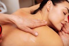 Donna pacifica e rilassata che ottiene la sua parte posteriore massaggiata con olio profumato immagini stock libere da diritti