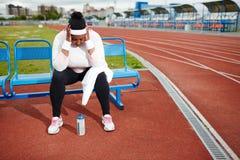 Donna paffuta che recupera dopo l'allenamento duro allo stadio di atletica Fotografie Stock Libere da Diritti