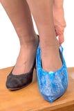 Donna in pantofole e soprascarpe Fotografia Stock