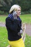 Donna in parco con un telefono Immagini Stock