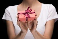 Donna parziale di vista che mostra regalo in mani sul nero Fotografia Stock Libera da Diritti