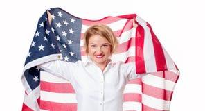 Donna patriottica sorridente che tiene la bandiera degli Stati Uniti U.S.A. celebra il 4 luglio fotografia stock libera da diritti