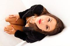 Donna in pelliccia nera che osserva in su Fotografie Stock