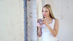 Donna pensierosa adorabile del colpo medio che gode della bevanda bevente della rottura dalla tazza e che considera finestra archivi video