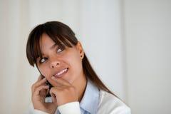 Donna pensierosa che cerca parlante sul cellulare Immagini Stock