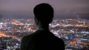 Donna pensierosa che esamina la citt? di notte dal grattacielo archivi video