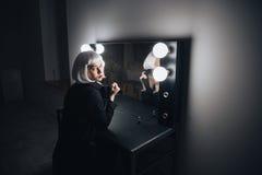 Donna pensierosa che si siede vicino allo specchio con le lampadine nello spogliatoio Immagini Stock Libere da Diritti
