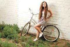 Donna pensierosa con la bici della città che pende indietro contro il muro di mattoni bianco nel retro colpo di colore di estate Fotografia Stock