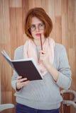 donna pensierosa dei pantaloni a vita bassa con un blocco note e una matita Fotografia Stock
