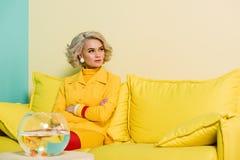 donna pensierosa in retro abbigliamento con il pesce dorato in acquario sulla tavola all'appartamento variopinto, bambola Immagini Stock Libere da Diritti