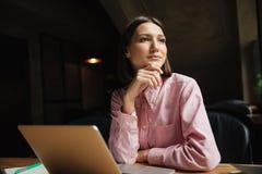 Donna pensierosa sorridente che si siede dalla tavola in caffè Fotografia Stock Libera da Diritti