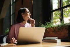 Donna pensierosa sorridente che si siede dalla tavola in caffè Immagine Stock Libera da Diritti