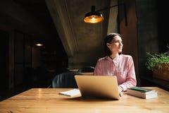 Donna pensierosa spensierata che si siede dalla tavola in caffè Immagine Stock Libera da Diritti