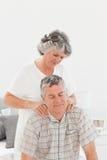Donna pensionata che dà un massaggio al suo marito Fotografia Stock Libera da Diritti