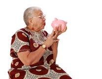 Donna pensionata che holkding banca piggy Fotografia Stock Libera da Diritti