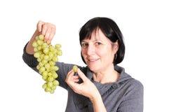 Donna pensionata che mangia l'uva Fotografie Stock