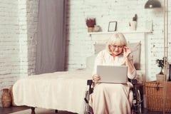 Donna pensionata handicap astuto che per mezzo del computer portatile a casa immagini stock