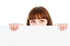 Donna Pensive che dà una occhiata sopra il tabellone per le affissioni in bianco Fotografia Stock Libera da Diritti