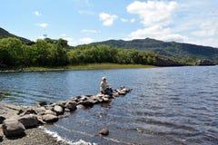 Donna per bagnare i vostri piedi nel lago immagine stock