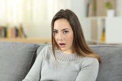 Donna perplessa che esamina macchina fotografica a casa fotografia stock