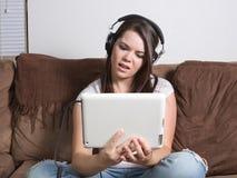 Donna perplessa che guarda scorrendo media sulla compressa Fotografia Stock Libera da Diritti