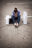 Donna persa che si siede nel parcheggio con i sacchetti Fotografia Stock Libera da Diritti