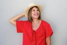 Donna più anziana attraente che ride con il cappello contro il fondo grigio Immagine Stock