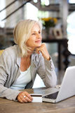 Donna più anziana attraente con il computer portatile e la carta di credito Immagine Stock