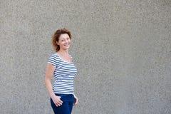 Donna più anziana attraente con la camicia a strisce che sorride contro la parete Fotografie Stock Libere da Diritti