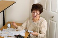 Donna più anziana che esprime scossa da tutte le sue fatture finanziarie Immagini Stock Libere da Diritti