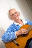Donna più anziana che gioca chitarra. fotografie stock