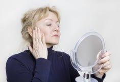 Donna più anziana che guarda in specchio Fotografia Stock