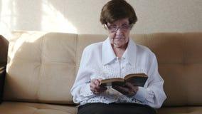 Donna più anziana che legge un libro a casa stock footage