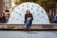 Donna più anziana che per mezzo della fontana O di Stuttgart Koenigsstrasse del telefono cellulare Immagine Stock Libera da Diritti