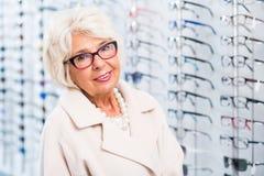 Donna più anziana che prova sui vetri immagine stock