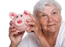 Donna più anziana che scuote porcellino salvadanaio divertente Immagine Stock