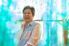 Donna più anziana che sorride alla macchina fotografica femmina anziana felice che si rilassa fuori Fotografia Stock