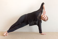 Donna più anziana che sorride nella posizione del lato di yoga Fotografie Stock