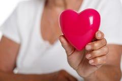 Donna più anziana che tiene il cuore rosso del giocattolo davanti al suo petto immagini stock libere da diritti