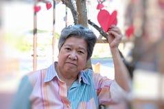 Donna più anziana che tiene la carta rossa del cuore & che sorride alla macchina fotografica E felice Fotografia Stock