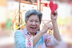 Donna più anziana che tiene la carta rossa del cuore & che sorride alla macchina fotografica E felice Fotografia Stock Libera da Diritti