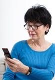 Donna più anziana con il cellulare immagini stock libere da diritti
