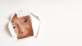 Donna più anziana curiosa che osserva attraverso il foro lo spazio della copia Fotografia Stock