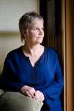 Donna più anziana dall'indicatore luminoso della finestra Immagini Stock