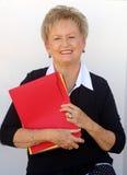 Donna più anziana di affari con i dispositivi di piegatura di archivio Immagine Stock