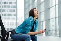 Donna più anziana di risata che si siede con il telefono cellulare Immagine Stock Libera da Diritti