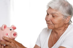 Donna più anziana felice e misteriosa che giudica porcellino salvadanaio divertente disponibile Immagine Stock