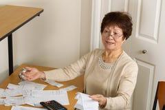 Donna più anziana frustrata con le sue fatture finanziarie Fotografia Stock