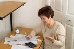 Donna più anziana frustrata da tutte le sue fatture finanziarie Immagini Stock